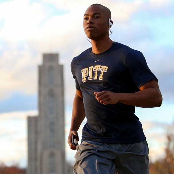 A young man wearing a Pitt shirt jogs with the Cathedral of Learning in the background