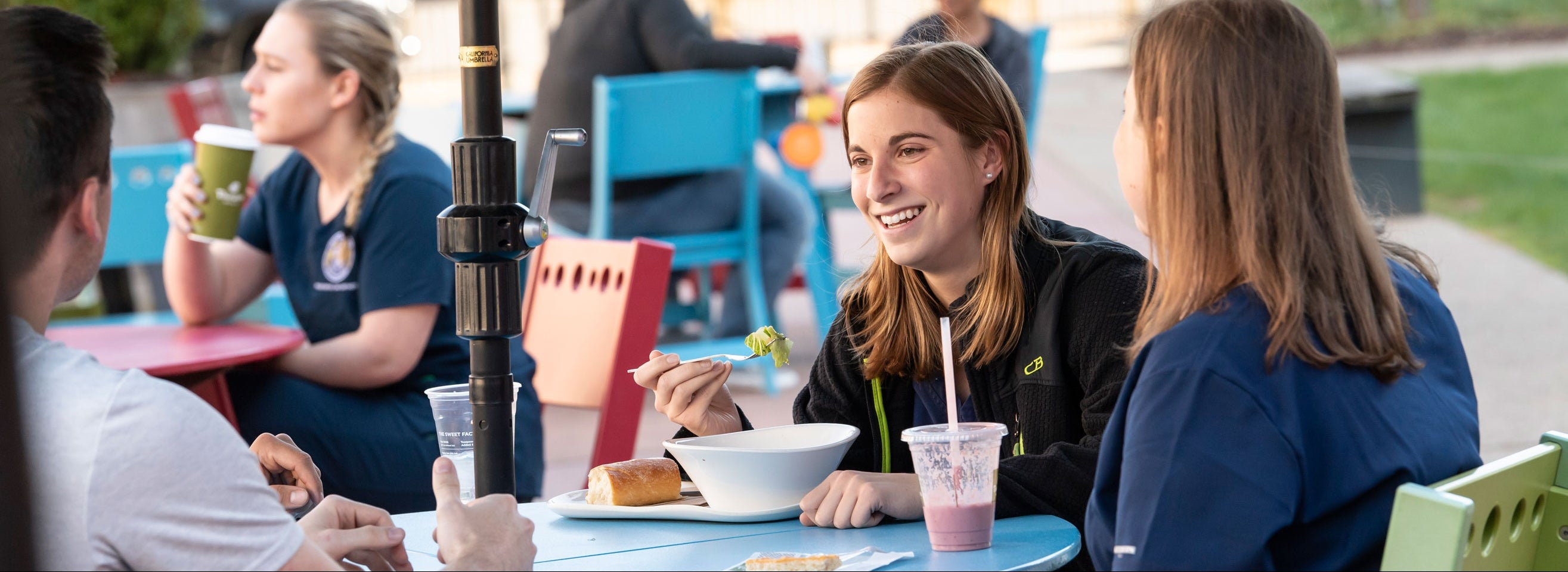 A woman eats a meal while dining outdoors with friends