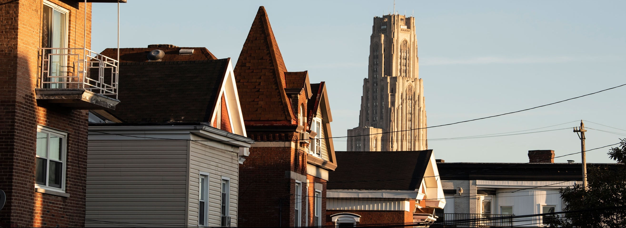 The rooftops of Oakland houses with the Cathedral of Learning in the background