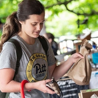 A student purchases items at the Pitt Farmers Market